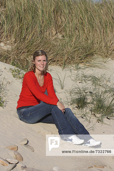 Young blonde woman outdoors. Sitting on sand dune at the beach.
