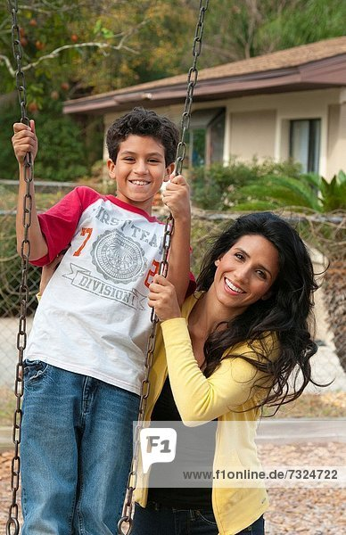 Hispanic single mother and som age 11 on swing in park at playground near home outdoors