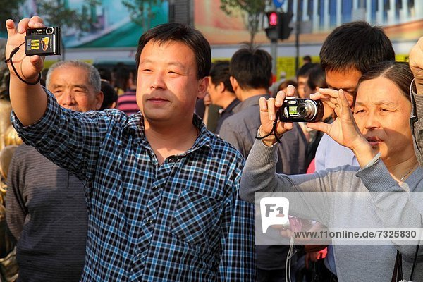 China  Shanghai  Huangpu District  East Nanjing Road  Asian  man  woman  National Day Golden Week  pedestrians  camera  taking picture
