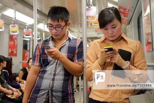 stehend  Frau  Mann  Kurznachricht  fahren  Öffentlicher Verkehr  U-Bahn  China  Shanghai  Smartphone