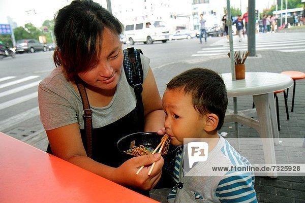 Frau  Eßstäbchen  Junge - Person  Sohn  Cafe  Restaurant  essen  essend  isst  Pasta  Nudel  China  Mutter - Mensch  füttern  Shanghai