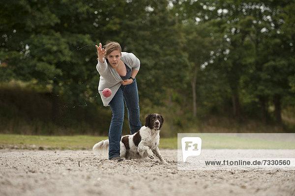 Frau spielt mit einem Kleinen Münsterländer