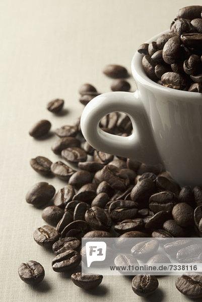 Kaffeebohnen in und um eine Kaffeetasse herum