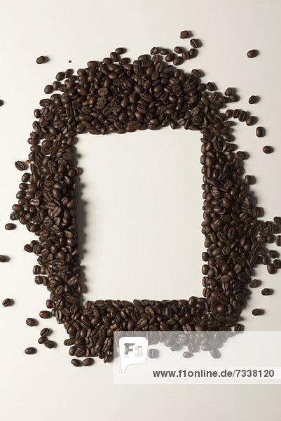Kaffeebohnen um eine rechteckige Form angeordnet