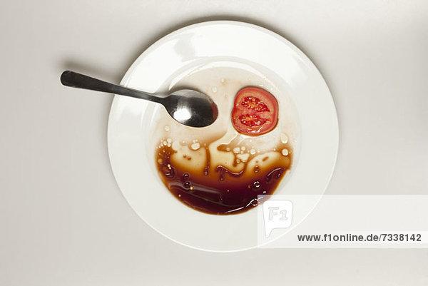 Abstraktes Gesicht aus Tomate  Löffel  Teller und Balsamico-Essig