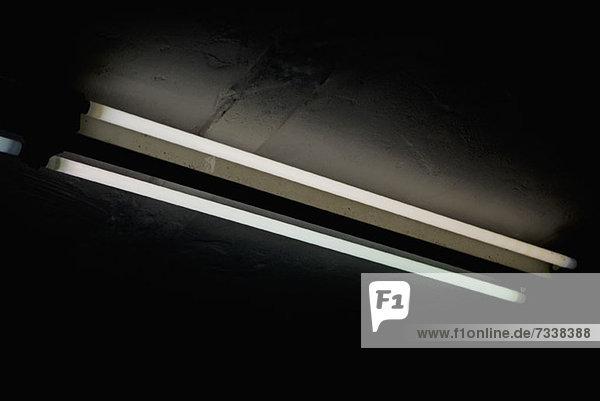 Zwei Röhrenleuchten umgeben von Dunkelheit