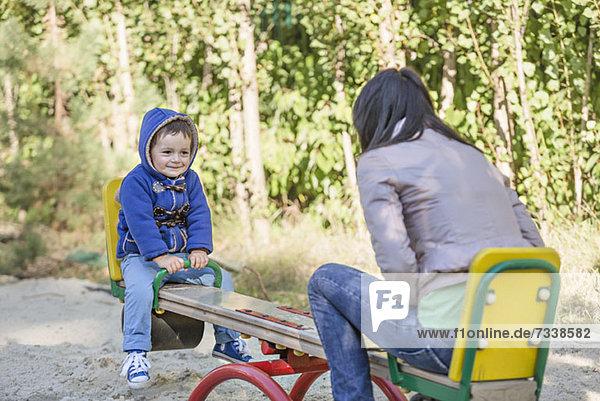 Eine junge Mutter und ihr kleiner Sohn auf einer Wippe auf einem Spielplatz