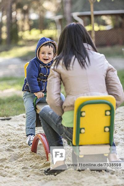 Eine Mutter und ihr Sohn auf einer Wippe auf einem Spielplatz