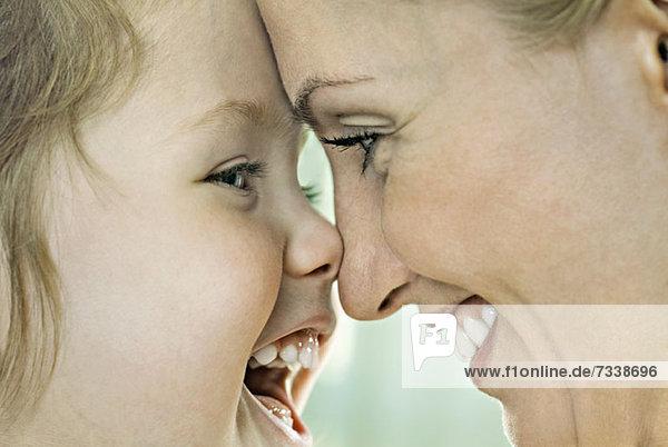 Ein lachendes Mädchen  das mit seiner lächelnden Mutter die Nase berührt  Nahaufnahme