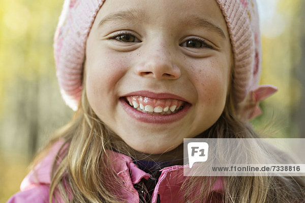 A cheerful young girl wearing a pink knit hat and grinning
