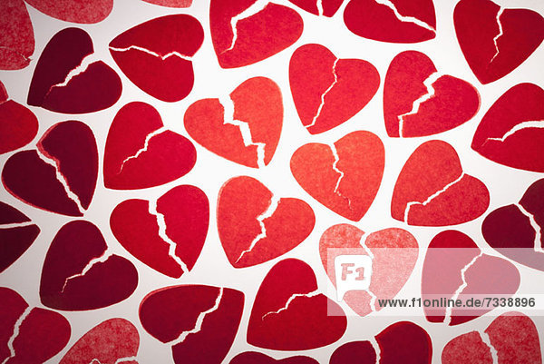 Ein Haufen rotes Seidenpapier  gebrochene Herzen.