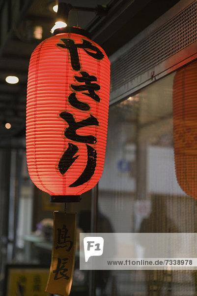 Japanische Papierlaterne  die außerhalb der Ladenfront hängt