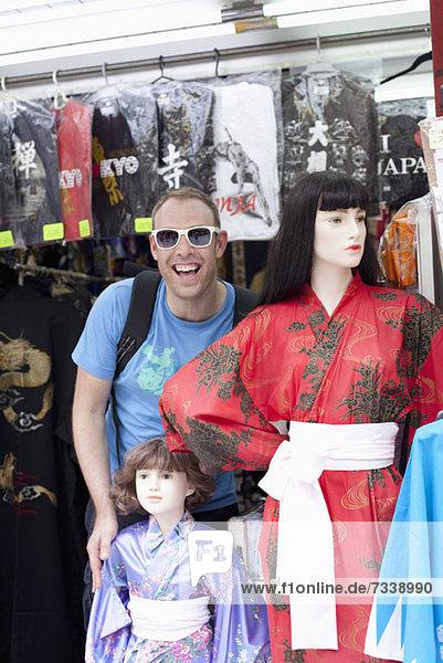 Tourist steht neben weiblichen Schaufensterpuppen mit Kimonos