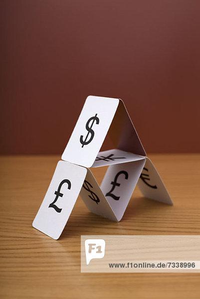 Ein Kartenhaus in verschiedenen Währungen