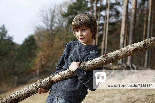 Ein Junge mit einem großen Ast in einem Waldgebiet