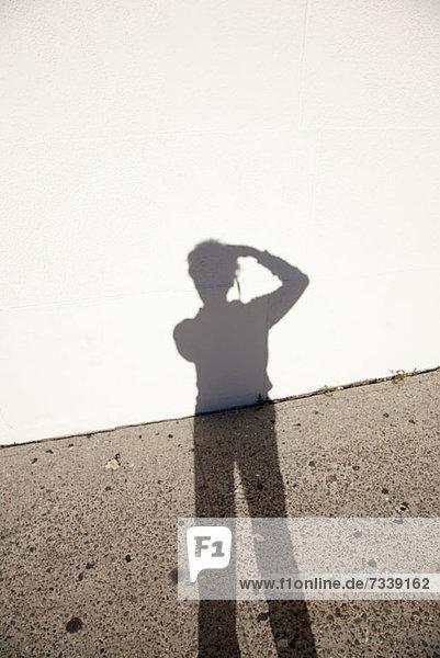 Schatten des Fotografen gegen Boden und Wand