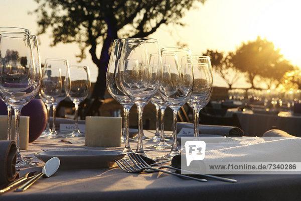 Gedeckter Tisch bei einer Hochzeitsfeier im Olivenhain bei Sonnenuntergang  Mallorca  Spanien  Europa