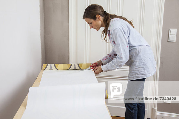 Young woman preparing wallpaper for wallpapering the walls