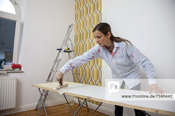 Young woman preparing wallpaper for wallpapering a wall