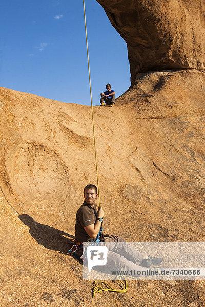 Junger Mann beim Abseilen vom Bogenfels  Spitzkoppe-Gebiet  Damaraland  Namibia  Afrika
