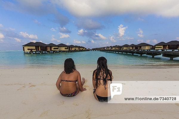 Zwei Mädchen  etwa 15 und 19 Jahre  sitzen am Strand an einer Lagune  hinten Paradise Island  Lankanfinolhu  Nord-Male-Atoll  Republik Malediven  Indischer Ozean  Asien