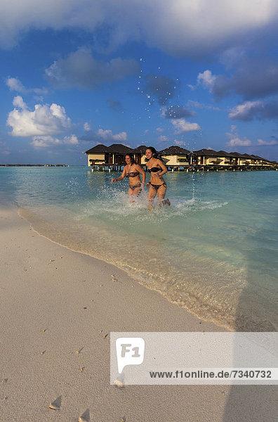 Zwei Mädchen  etwa 15 und 19 Jahre  rennen fröhlich am Strand an einer Lagune  hinten Paradise Island  Lankanfinolhu  Nord-Male-Atoll  Republik Malediven  Indischer Ozean  Asien