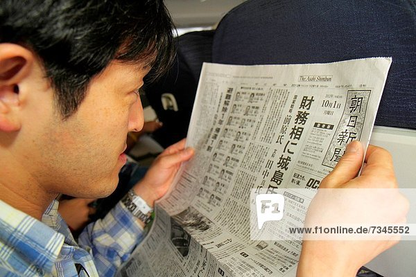 Illinois  Chicago  O´Hare International Airport  ORD  onboard  United  commercial airliner  cabin  Asian  man  reading  passenger  Japanese  language  symbols  Kanji