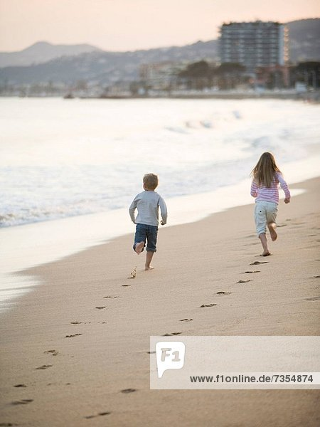 brother and sister running at the beach