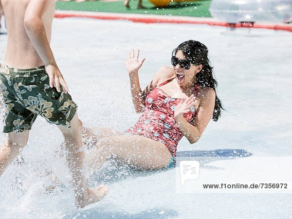 woman getting splashed at a waterpark