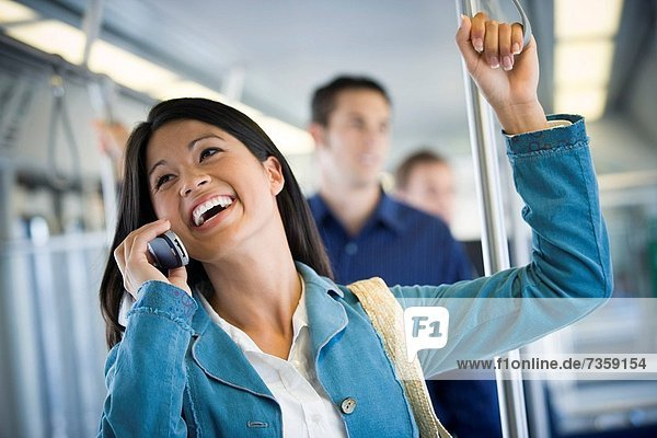 Young woman talking on a mobile phone in a passenger train