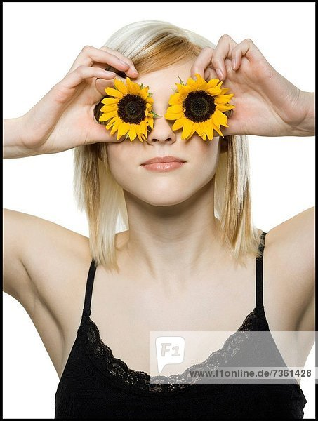 Close_up of a young woman holding sunflowers in front of her eyes