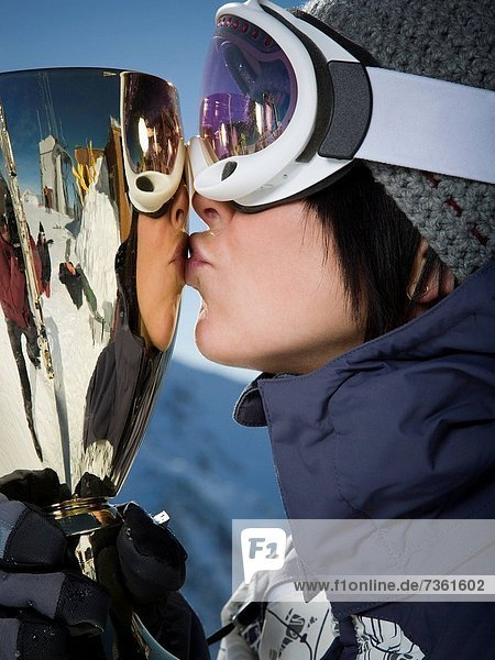 Close_up of a young woman kissing a trophy