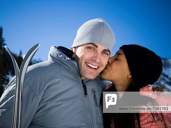 Close_up of a young woman kissing a young man on the cheek