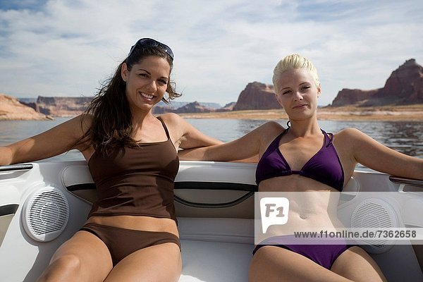 Portrait of two mid adult women sunbathing in a boat