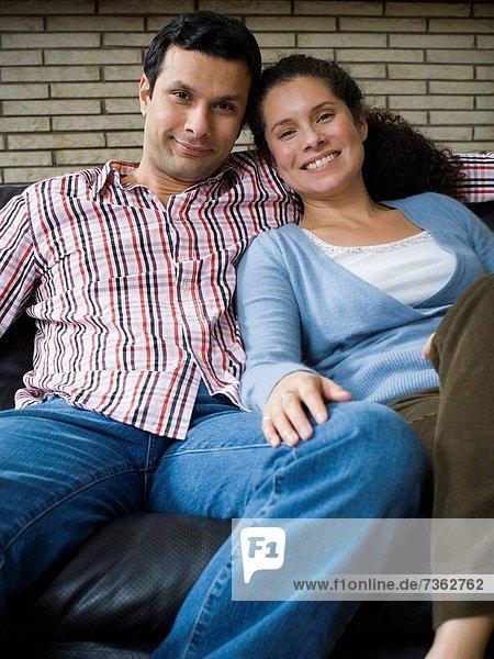 Portrait von einem Paar auf einer Couch sitzen und lächelnd