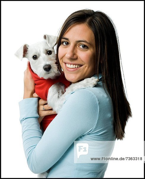 Portrait of a young woman holding a dog in her arms and smiling