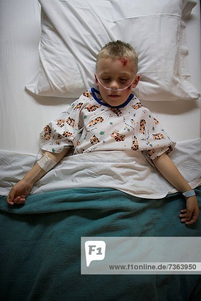 High angle view of a boy lying in a hospital bed breathing through a tube