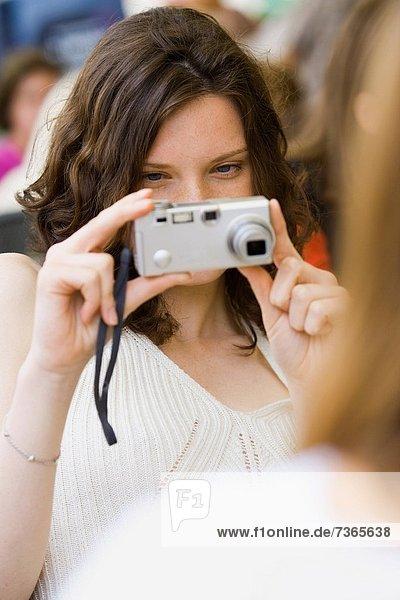 Teenage girl holding a digital camera