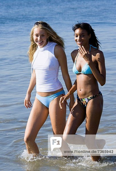 Two young women wading in the water on the beach