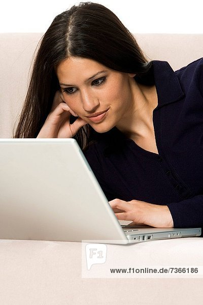 Close_up of a young woman lying on a couch and using a laptop