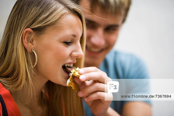 Close_up of a young man feeding a young woman a piece of chocolate