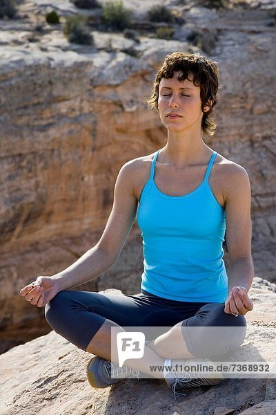 Woman sitting cross legged on rock outdoors doing yoga