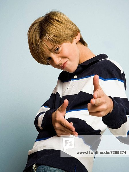 Portrait of boy making shooting gesture with hands