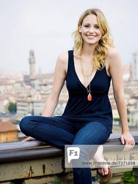 Außenaufnahme  sitzend  Frau  lächeln  Großstadt  Hintergrund  freie Natur