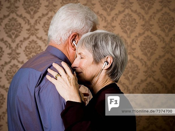 Profile of an elderly couple dancing and listening to music