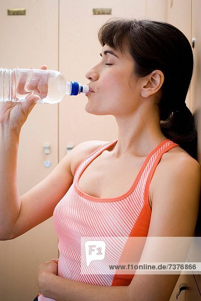 Profile of a young woman drinking water from a water bottle