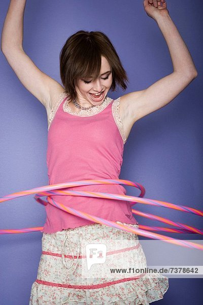 Close_up of a teenage girl spinning hula hoops around his waist