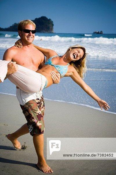 Mann trägt Freundin am Strand