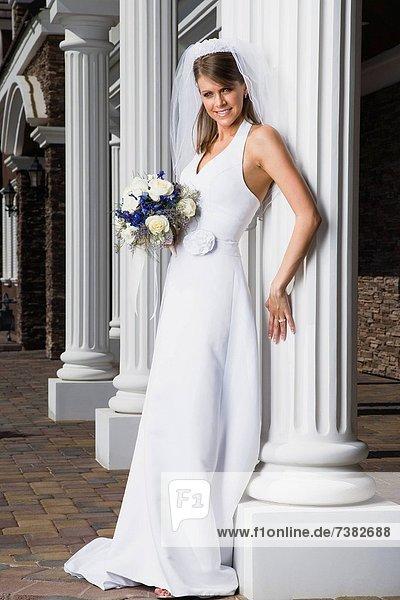 Porträt von eine Braut hält ein Blumenstrauß und lächelnd