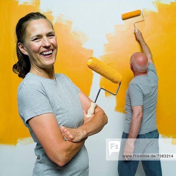 Senior  Senioren  Racken  Coraciidae  Portrait  Frau  Mann  Wand  halten  streichen  streicht  streichend  anstreichen  anstreichend  Farbe  Farben  bemalen